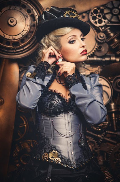 Woman wearing blue steampunk clothing: corset, jacket, skirt, hat, striped stockings, jewelry