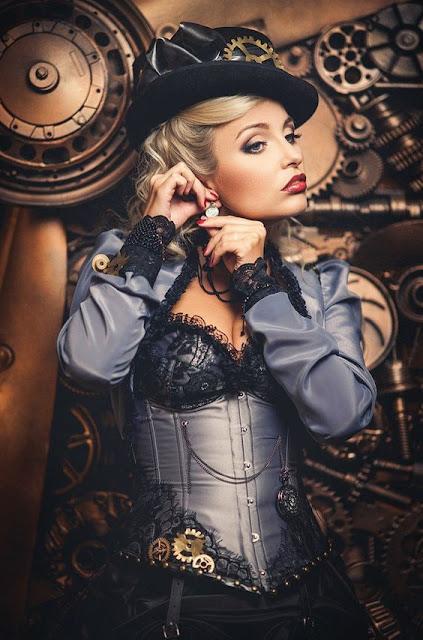 Woman wearing blue steampunk clothing: corset, jacket, skirt, hat, striped stockings, jewelry