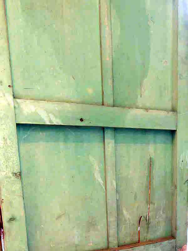 Green wooden outhouse door with a crack