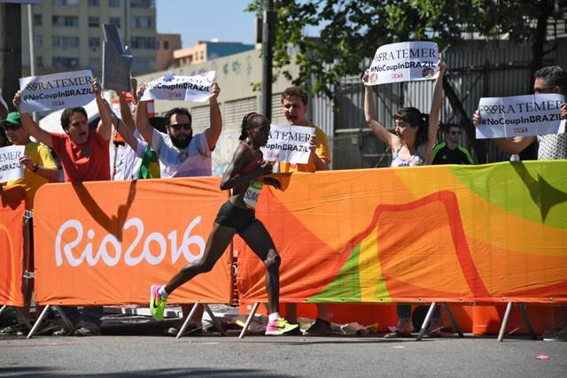 """Maratonista queniana Jemima Jelagat Sumgong corre em frente de manifestantes com cartazes de """"Fora Temer"""" no Rio de Janeiro, dia 14 de agosto de 2016."""