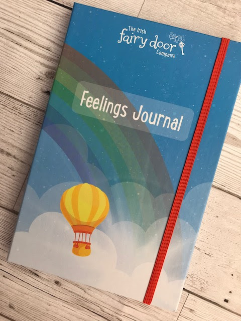 The journal, illustrated with a rainbow, clouds and hot air balloon