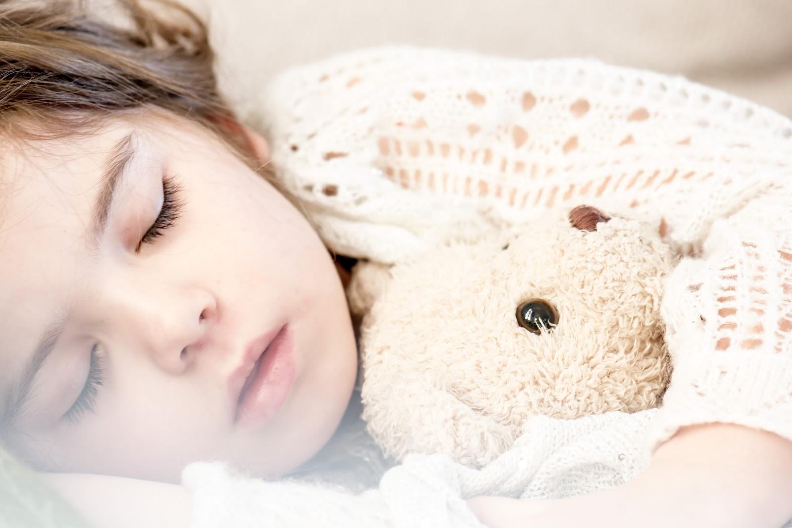 テディベアのぬいぐるみを抱きながら眠っている子供