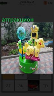 На асфальте стоит разноцветный детский аттракцион