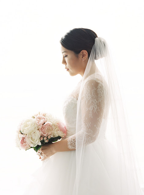 A portrait of Jin in her wedding gown with pink and white bridal bouquet