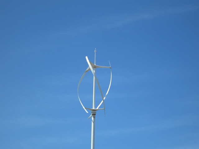 A whirligig type wind turbine - small - white - against blue sky