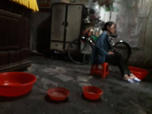 Dưới nền nhà đặt nhiều vật dụng để hứng nước mưa chảy xuống từ mái nhà