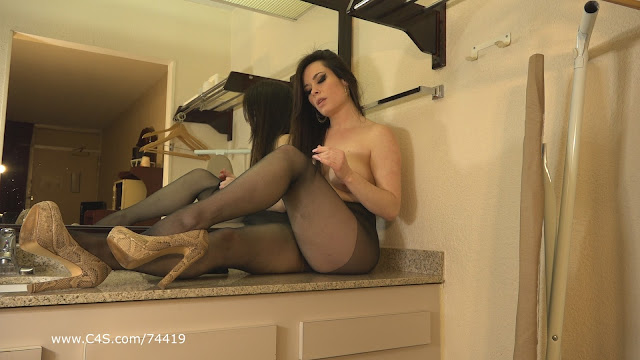 Jasmin Jai sitting on a hotel bathroom sink, topless, wearing pantyhose