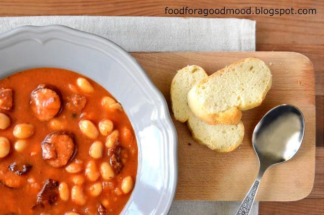 """Fasolka po bretońsku z Bretanią ma tyle wspólnego, co ryba po grecku z Grecją :) Jednak prawda jest taka, że dobrze przyrządzona nęci wspaniałym smakiem i zapachem. Klucz do sukcesu to dodatek ziół: cząbru i majeranku, dobry przecier pomidorowy i... hiszpańskie chorizo. Dokładnie! Pikantna, paprykowa kiełbasa to w tym wypadku to przysłowiowa """"kropka nad i"""". Pysznie łamie stereotyp i fajnie podkręca smak. Koniecznie spróbujcie :)"""