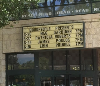 The photograph shows a marquee on an exterior stone wall above glass doors. It reads: Book People Presents with four author names and 6-30 Erin Pringle 7 PM