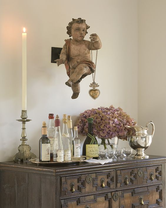 Antique Spanish Colonial campaign table used as bar with magnificent antique cherub and ex voto milagro hear presiding over it in the Santa Fe home of Peter Vitale. #frenchcountry #frenchantiques #interiordesign #petervitale