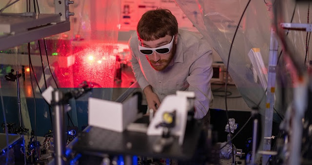 Rice University graduate student Tom Langin makes an adjustment to an experiment that uses dozens of lasers of varying wavelengths to laser-cool ions in a neutral plasma that is made by first laser-cooling strontium atoms and then ionizing them with a high-power laser. (Photo by Brandon Martin/Rice University)