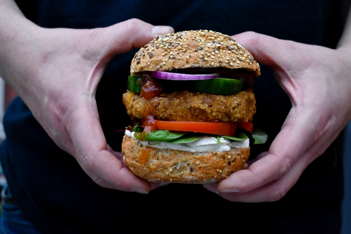 Man's hands holding an Instant vegan haggis, neeps and tatties burgers