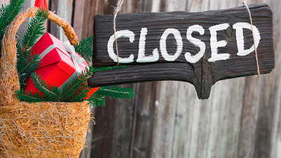 Rustic sign hanging next to a basket of holiday gifts alongside a fence that reads closed