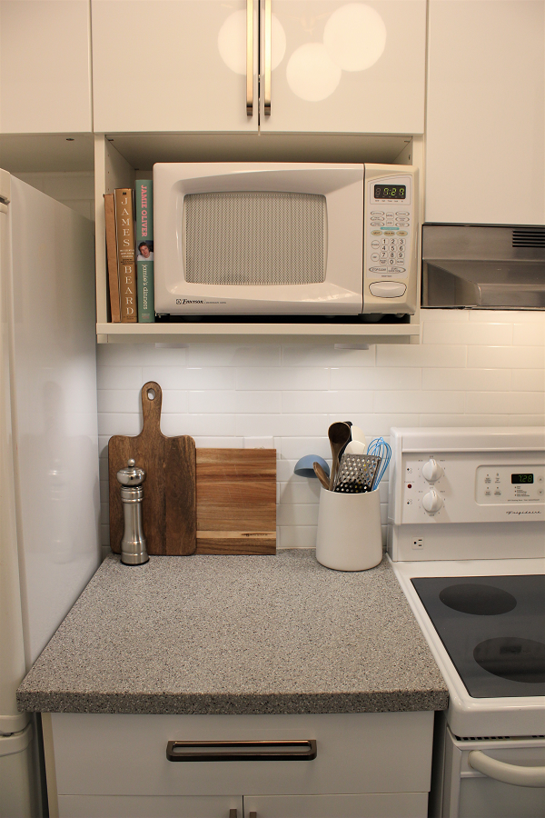 Microwave above a grey counter and white back splash
