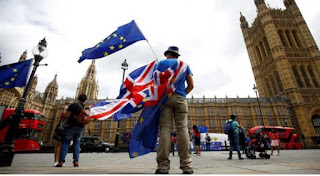Man Flying anEU and Brittish flag in front of the UK parliamentary building