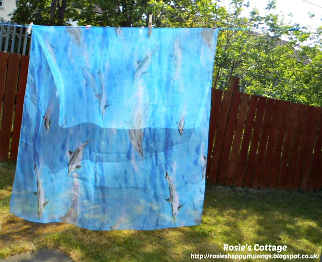 Dolphins swim happily across a pretty, sheer scarf on the laundry line.