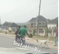 Man On A Motorcycle Drags A Malnourished Dog Along A Road In Calabar