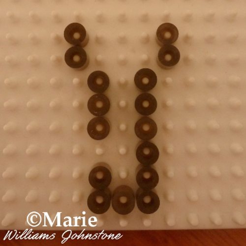 Adding some gold color Perler beads to a white pegboard