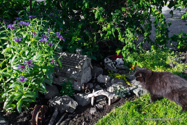 Rock walkways guide you to this farm-styled fairy garden with a barn birdhouse!