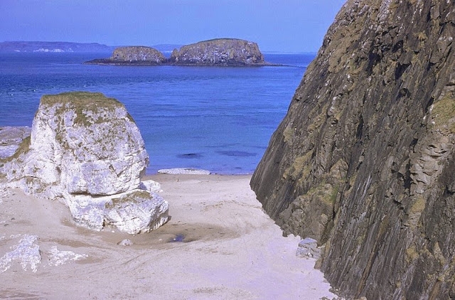 Just E. of Ballintoy Harbour, Co. Antrim. Looking E. Upper Chalk and Tertiary dolerite intrusions just east of Ballintoy Harbour, Co. Antrim. Intrusive plug of Bendoo on right-hand side with chalk stack in centre. Sheep Island still in centre middle distance with Rathlin Island on horizon. View facing east from small cave 200 yd. south-east of Ballintoy Harbour.