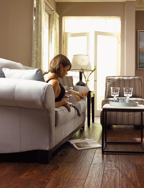 Woman relaxing in a sitting room with beautiful wood flooring