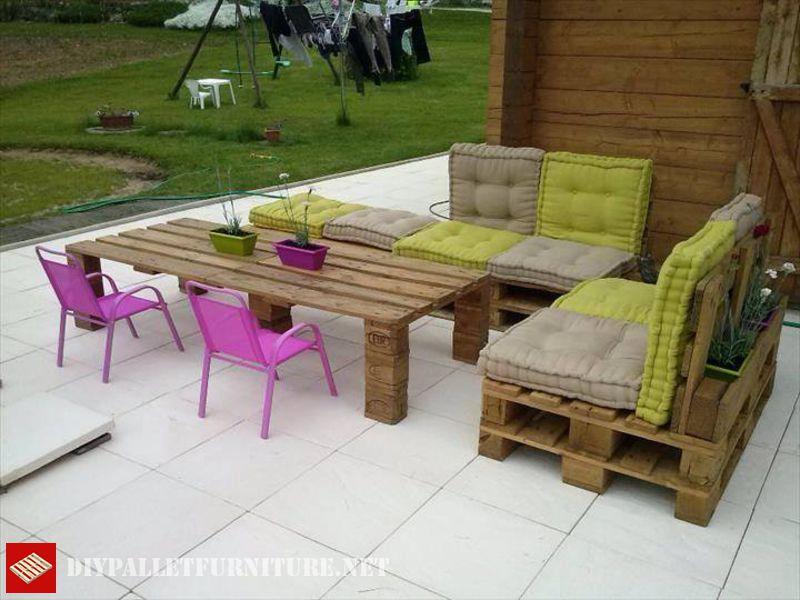 aqu podis ver una terraza amueblada con sofas hecho con palets e incluso una mesa elevada la mesa es de suficiente altura para utilizarse