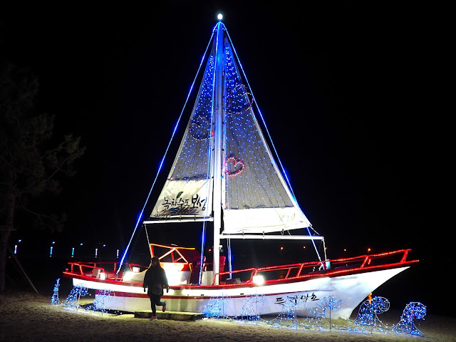 Sailing boat adorned with lights on the sand at the Light Festival at the Yulpo Beach area of Boseong Green Tea Plantation, South Korea