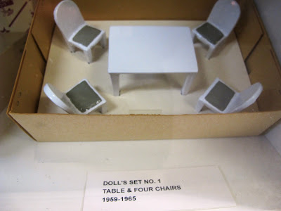 Set of metal dolls' house table and chairs displayed in its box.