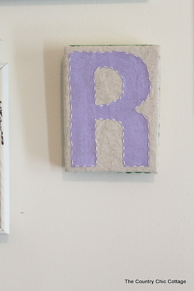 Monogram Wall Art -- use Styrofoam, fabric, and a little paint to create a one of a kind monogram wall art piece that will look great in your home.  Click to get the full instructions.