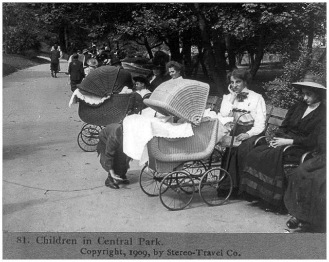 Children in Central Park. Women seated on benches, two baby carriages. 1909
