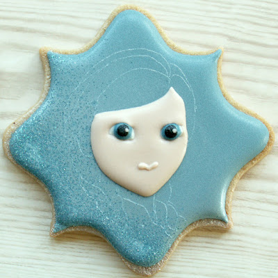 Decorated cookie with Anna from Frozen's eyes and face piped, by Honeycat Cookies