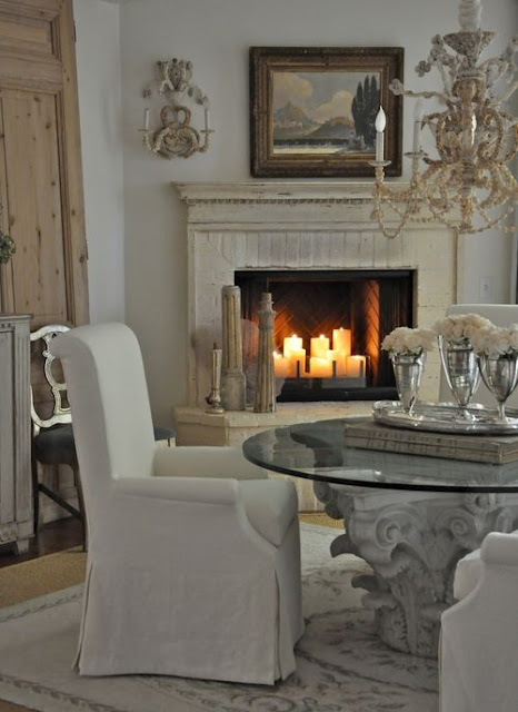 Romantic farmhouse style dining room with fireplace and slipcovered chairs by Giannetti Home