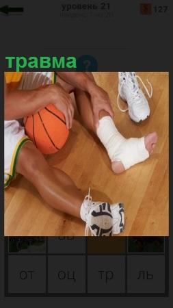 Баскетболист получил травму ноги и сидит на полу с мячем