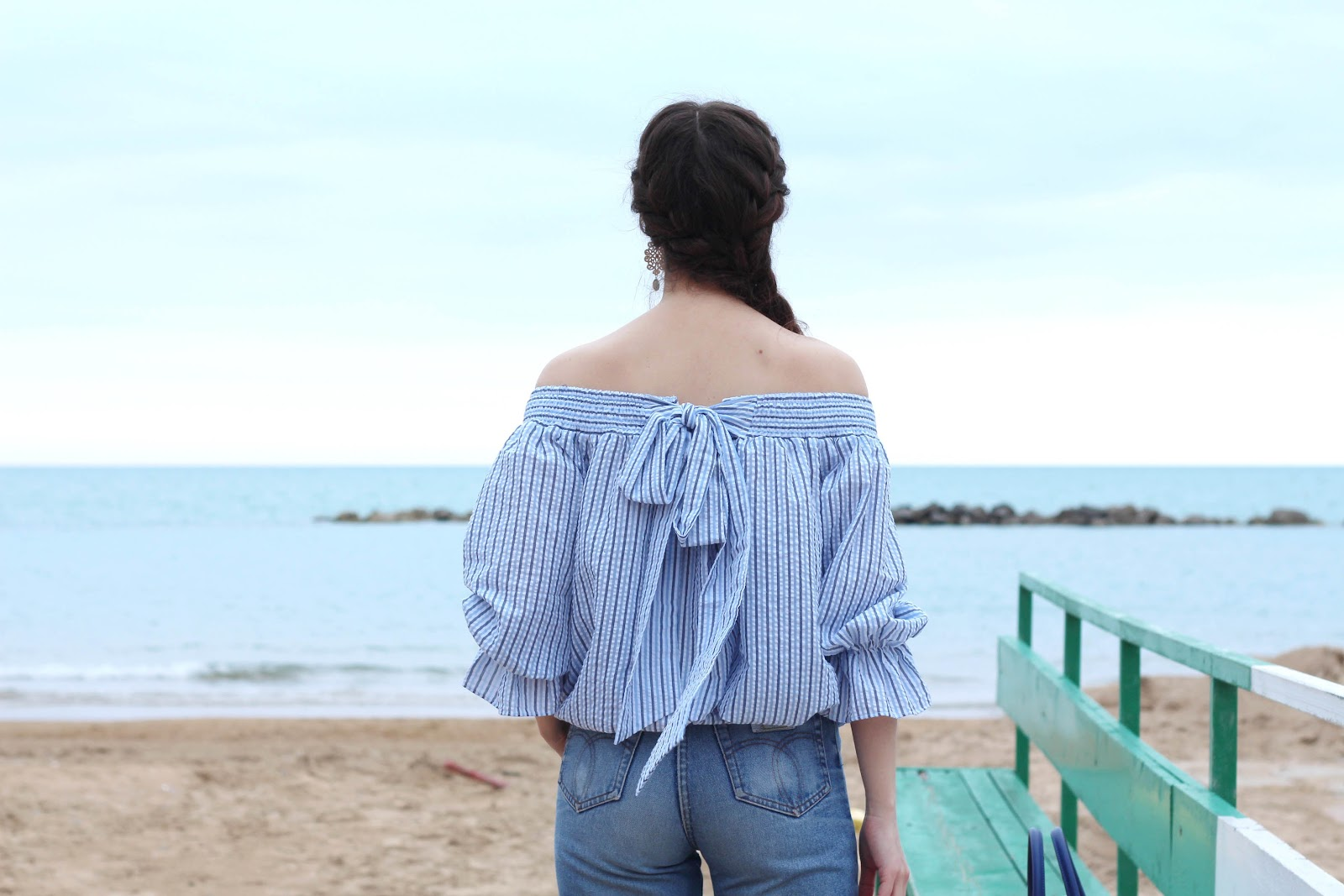 fashion style blogger outfit ootd italian girl italy vogue glamour pescara light blue bow off-the-shoulder top bluse chicwish trend denim jeans 90 calends blue bag borsa blu prospering flats ballerine shoes scarpe fabijoux earrings orecchini macramè braid hairstyle hair
