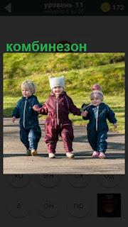 трое детей идут по дорожке в комбинезонах