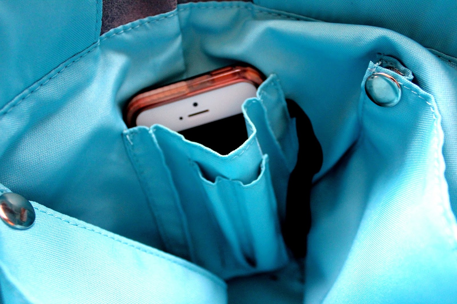 Turquoise interior of a handbag, a phone is visible in the phone holder.