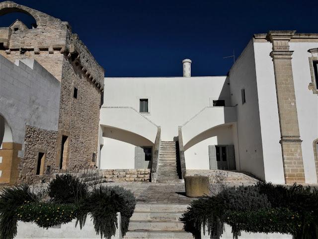 Una scala che porta all'appartamento superiore della masseria di colore bianco. A sinistra una torre in pietra