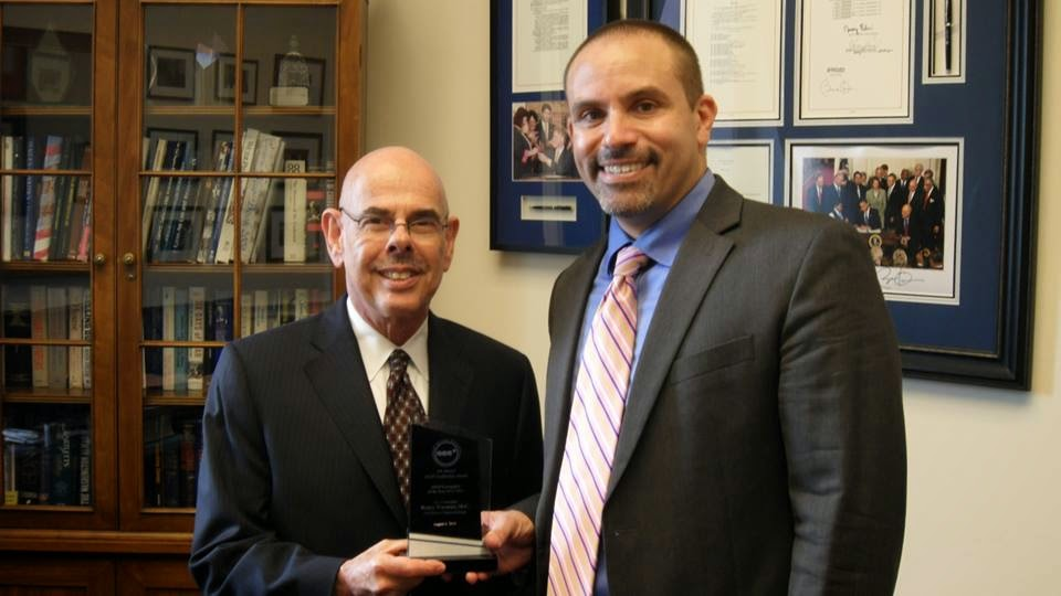 Photo of retired U.S. Congressman Henry Waxman being presented with an award by Brandon Macsata