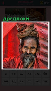 сидит мужчина в красной одежде и на голове у него дредлоки