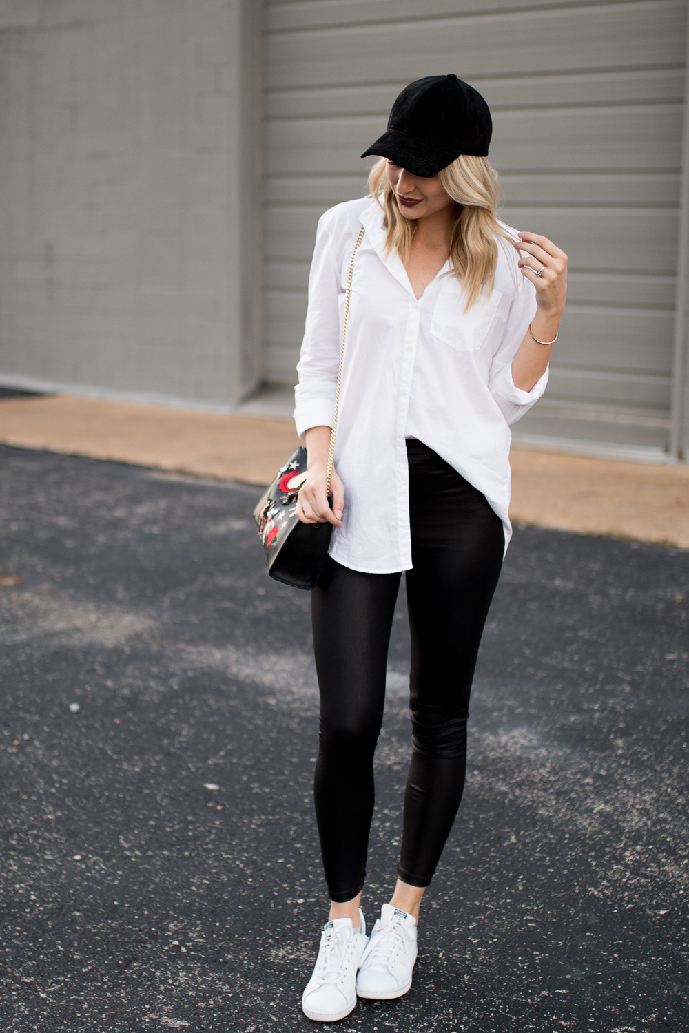 Easy weekend outfit: button-down, leather leggings, sneakers and a ball cap