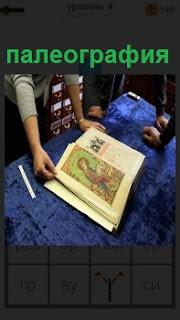 На столе развернута древняя рукопись с иллюстрацией, двое людей внимательно её рассматривают