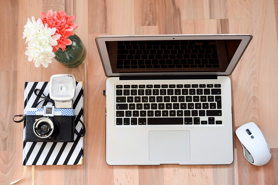 Laptop, books and flower vase
