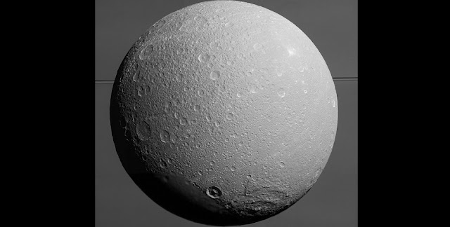 Dione with Saturn and its rings in the background. This image was taken by the Cassini spacecraft on Aug. 17, 2015 (NASA/JPL-Caltech/Space Science Institute)