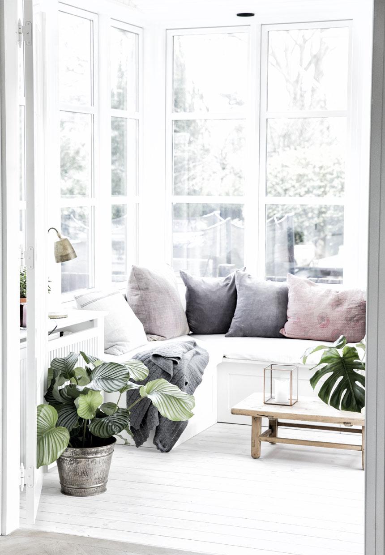 cozy corner with houseplants in Nordic villa interior rustic coffee table, pillows
