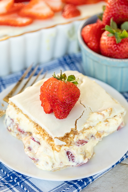 Strawberries and Cream Eclair Cake - delicious no-bake dessert! Vanilla pudding, cool whip, strawberries and graham crackers layered and topped with vanilla frosting. It gets better the longer it sits in the fridge - it is just SO hard to wait to eat it. SOOO good. People go nuts over this easy dessert recipe! #dessert #cake #nobake
