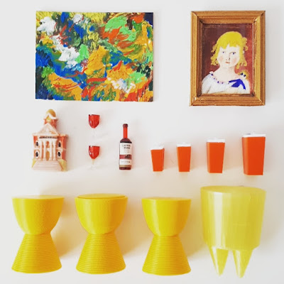 Flat lay of one-twelfth scale modern miniature items in colours of red, orange and yellow including paintings, Philippe Starck Prince Aha and Bubu stools, retro kitchen canisters and a bottle and glasses of red wine.