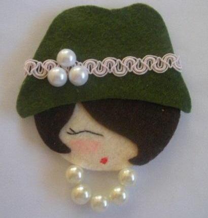 rosto de daminha em feltro com chapéu e contas