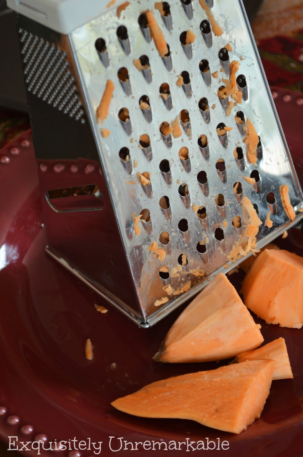 Shredding a sweet potato with a grater