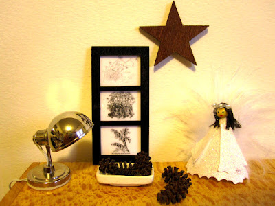 Modern miniature cupboard-top scene which includes a silver lamp, a bowl of pinecones, a three-section picture, a Christmas angel and a wooden star on the wall.