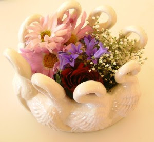 Garden flowers in a vase decorated with swans represents the Roman Moon Goddess Juno